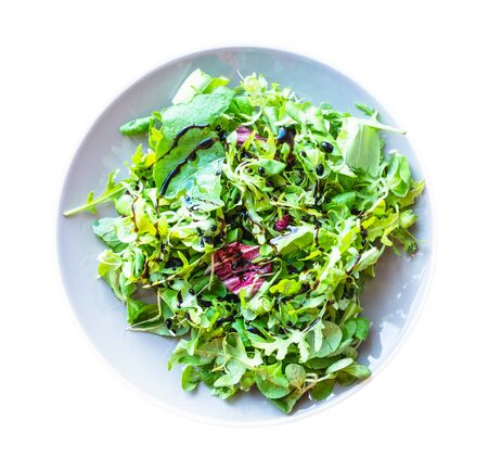 top view of mesclun salad from arugula, mache, radicchio, etc, greens with dressing of balsamic vinegar and olive oil on gray plate cut out on white background Banco de Imagens