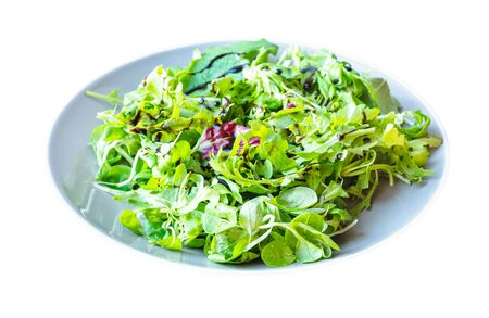 mesclun salad from arugula, mache, radicchio, etc, greens with dressing of balsamic vinegar and olive oil on gray plate cut out on white background Banco de Imagens