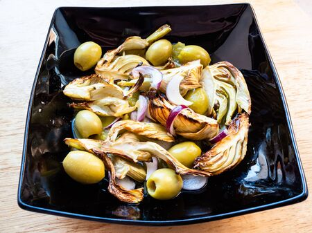 french cuisine - baked fennel stalk with olives and red onion and dressing of orange, lemon juice and olive oil on black plate on wooden board