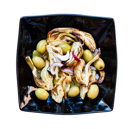 french cuisine - top view of baked fennel stalk with olives and red onion and dressing of orange, lemon juice and olive oil on black plate cutout on white background