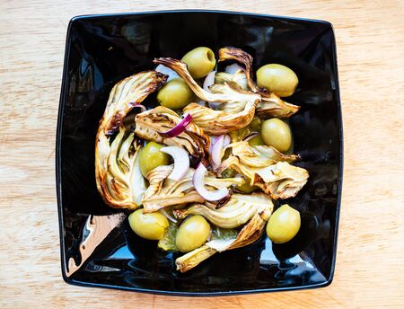french cuisine - top view of baked fennel stalk with olives and red onion and dressing of orange, lemon juice and olive oil on black plate on wooden table Banco de Imagens