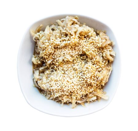 french cuisine - top view of fresh grated kohlrabi salad with sesame seeds and dressing of honey, balsamic vinegar and olive oil in white ceramic bowl cutout on white background