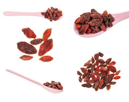 dry goji berries (wolf berry) in piles and spoons cut out on white background