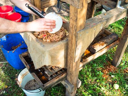 laying crushed fresh apples in the form of wooden press for squeezing natural juice to produce cider in village 스톡 콘텐츠