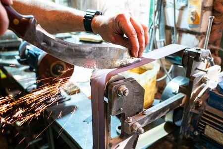 sharpening Kukri traditional Nepali knife on grinding machine in village workshop