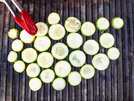 cooking of slices of zucchini on grate of outdoor grill