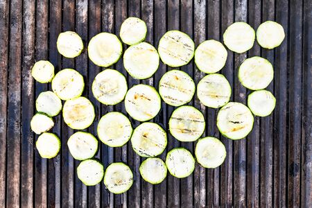 top view of roasted slices of zucchini on grate of outdoor grill