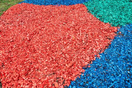 colored layers of wooden mulch on surface of soil on lawn