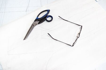 tailor's scissors and glasses lie on sheets of tracing paper with a pattern of a female dress on table