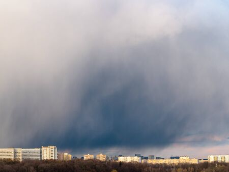 large storm cloud over urban houses in spring evening in Moscow city