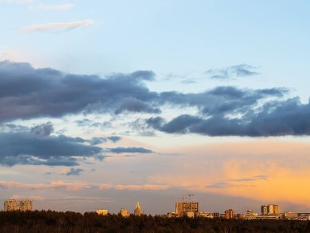dark clouds in blue sky over urban houses at spring sunset in Moscow city