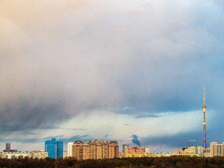 large rainy cloud over residential district at spring sunset in Moscow city