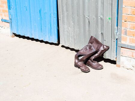 spring in city - thrown old winter leather boots near doors of outdoor garbage tank