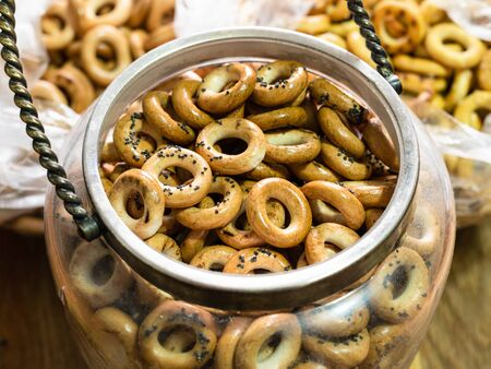 above view of many Sushki with poppy seeds (traditional Eastern European crunchy bread rings) in vintage glass jar on wooden home in home kitchen