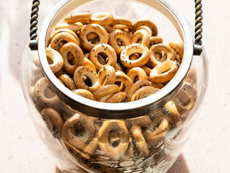 many Sushki with poppy seeds (traditional Eastern European crunchy bread rings) in vintage glass jar Stockfoto