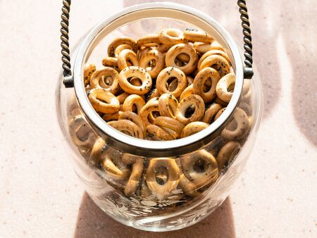 Sushki with poppy seeds (traditional Eastern European crunchy bread rings) in vintage glass jar on window sill in home kitchen