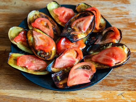sliced roasted eggplants with spice dip and fresh tomatoes on black plate on shabby wooden table at home kitchen