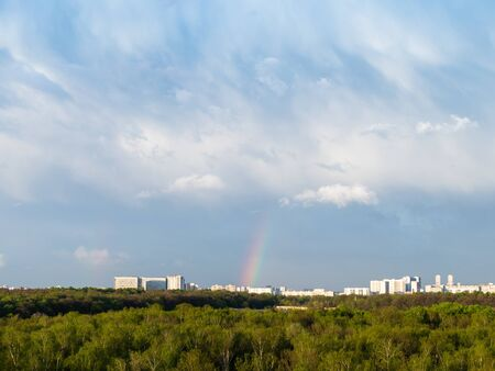 blue rainy clouds and rainbow over city on sunny spring day Stockfoto