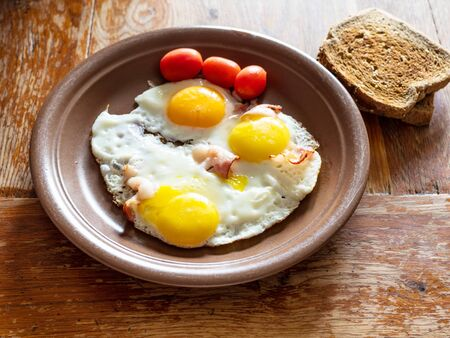 three fried eggs with bacon on brown ceramic plate on shabby wooden table at home kitchen Stockfoto