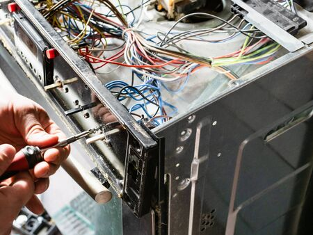 repairman fixes panel of old electric stove during repair in home kitchen