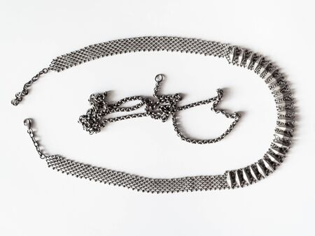 workshop for cleaning tarnished silver with aluminum foil and baking soda - tarnished vintage silver necklace and chain on white paper