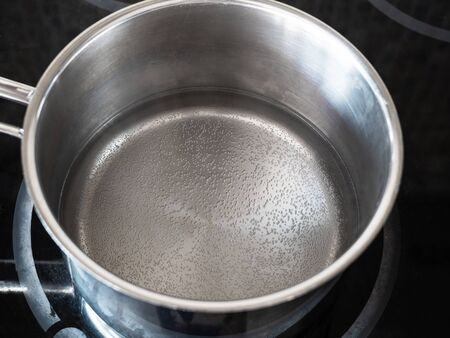 workshop for cleaning tarnished silver with aluminum foil and baking soda - water begins to boil in pot on kitchen electric stove Imagens