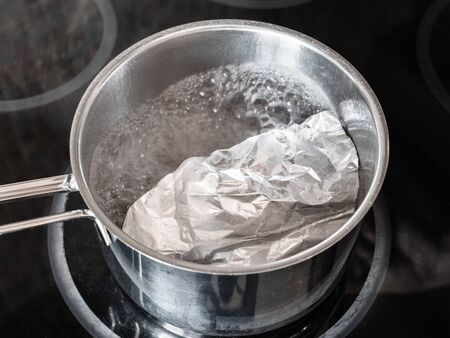 workshop for cleaning tarnished silver with aluminum foil and baking soda - boiling water solution of baking soda with aluminum foil and silver objects on electric stove