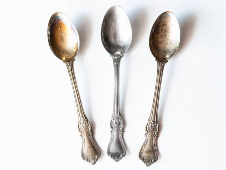 workshop for cleaning tarnished silver with aluminum foil and baking soda - two tarnished and one clean vintage silver spoons on white paper Archivio Fotografico