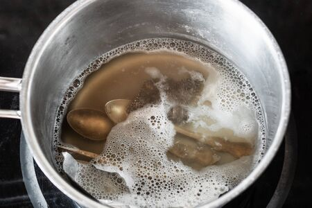 workshop for cleaning tarnished silver with aluminum foil and baking soda - silver cutlery in boiling solution of baking soda with aluminum foil in pot on electric stove