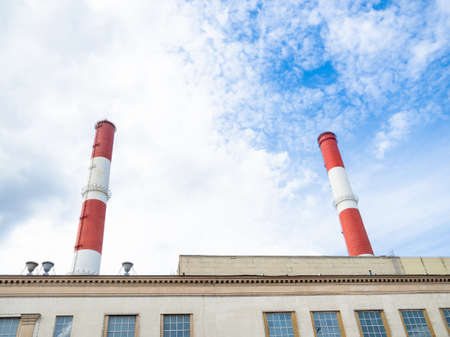 chimneys of city termal power station over industrial building on Sunday summer day in Moscow city