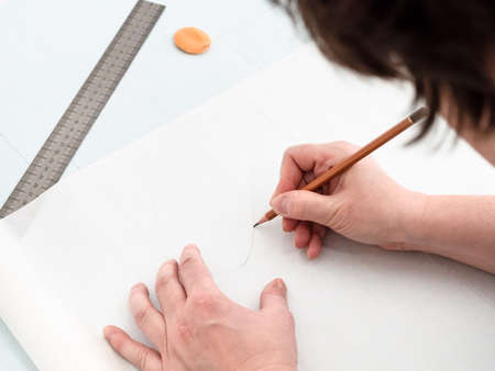 tailor copies pattern layout of dress with pencil and ruler on tracing-paper from graph paper at home