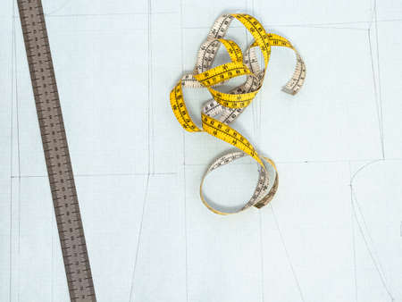 top view of tailor's measure tape and ruler on pattern layout of dress drawn on graph paper at home