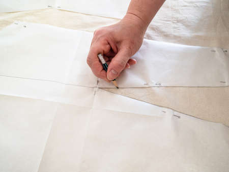 designer's hand draws sketch on calico fabric by pencil according with paper layouts of dress at home