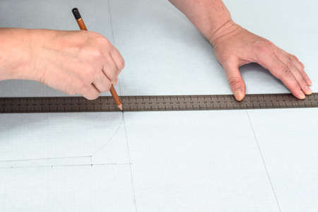 tailor's hands draw pattern layout of dress with pencil and ruler on graph paper at home