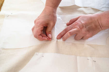 tailors's hand fixes paper cutting layouts of dress to calico cloth by pins on wooden table at home