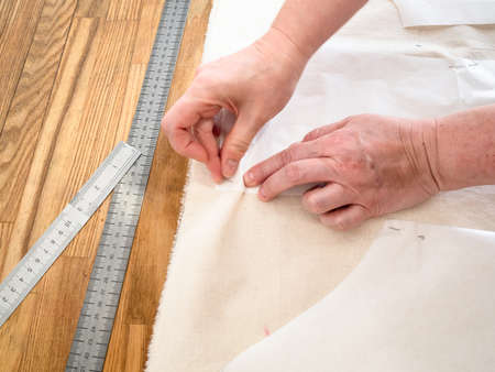 designer's hand fixes paper cutting layouts of dress to calico fabric by pins on wooden table at home Archivio Fotografico