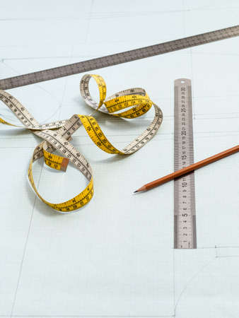measuring tape, rulers and pencil on pattern layout of dress drawn on graph paper at home