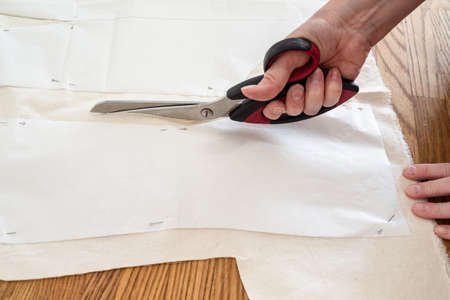 hand cuts mock-up fabric by scissors according with pattern layouts of dress on wooden table at home Archivio Fotografico