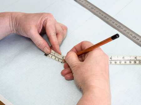 designer's hands draws pattern layout of dress with measure tape on graph paper at home