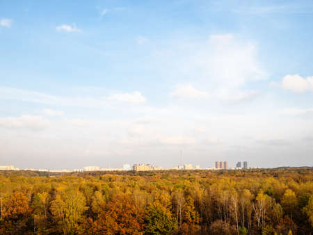 blue sky with white clouds over town and colorful forest on autumn afternoon Archivio Fotografico