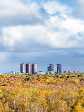 large rainy clouds over yellow forest and residential district on horizon on sunny autumn day