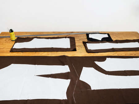view of pattern layouts of dress on brown fabric on wooden table at home