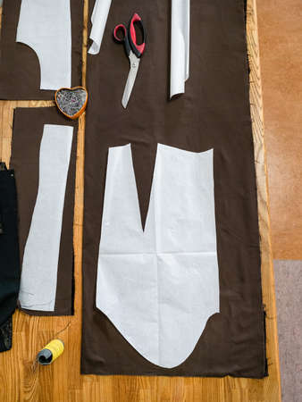 top view of sartorial tools and patterns layouts of dress on brown fabric on wooden table at home