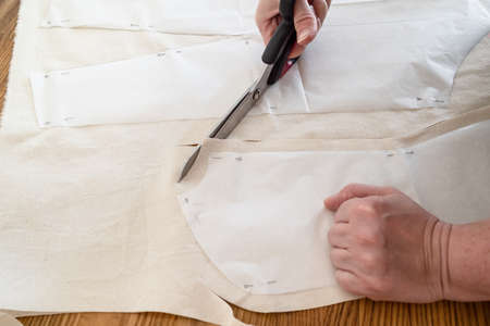 designer's hand cuts calico cloth by scissors according with paper layouts of dress on wooden table at home