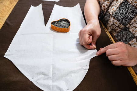 tailor fixes paper pattern layout of dress to brown fabric by pins on wooden table at home