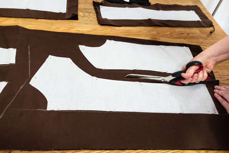female hand cuts brown fabric by scissors according with pattern layouts of dress on wooden table at home