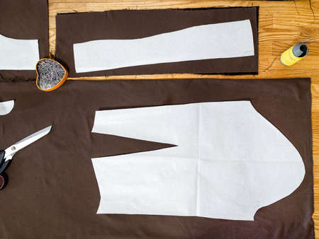 top view of paper layouts of pattern of dress on brown fabric on wooden table at home