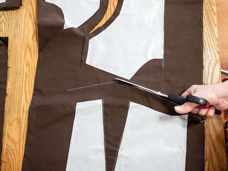 top view of hand cuts brown fabric by scissors according with pattern layouts of dress on wooden table at home