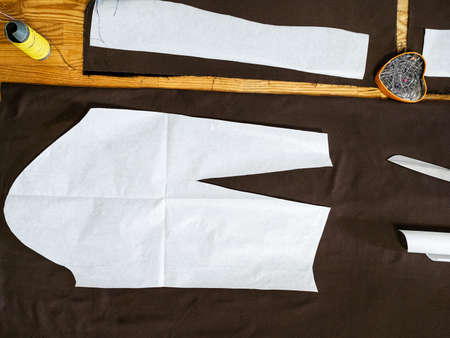 top view of paper pattern layout of dress on brown fabric on wooden table at home