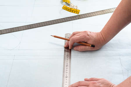 designer's hands with pencil and rulers on pattern layout of dress drawn on graph paper at home